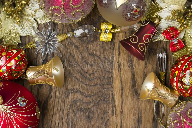 Christmas tree decoration. Christmas decoration ornament, new year toys of red and gold colors on wooden background, winter holidays and celebrations concept stock photo