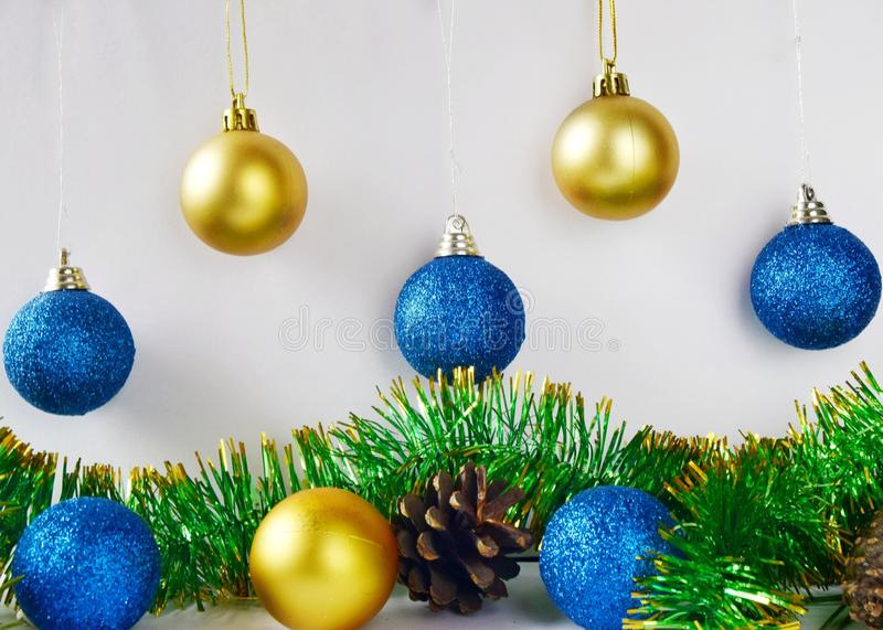 Christmas tree decorations blue and yellow balls on white background close up. Christmas tree decorations blue and yellow balls on white background with tinsel royalty free stock image