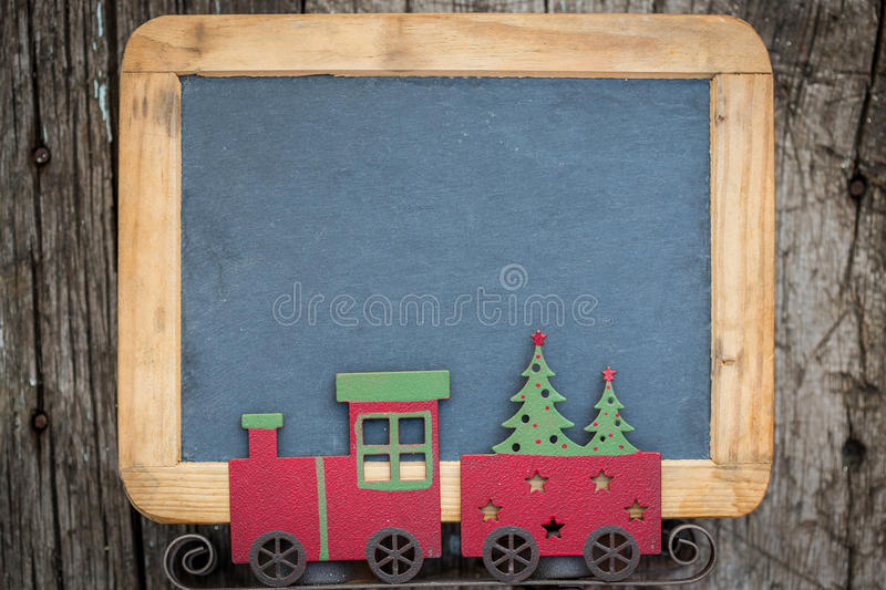 Christmas tree decorations border on vintage wooden blackboard stock photography