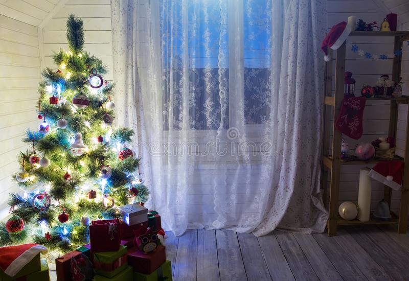 Christmas tree with Christmas decorations and gifts in mansard room.  stock image