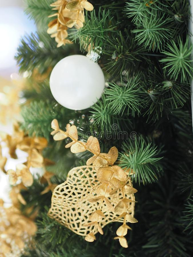 Christmas tree decorations have white ball, gold leaves on blurred of background. Closeup Christmas tree decorations have white ball, gold leaves on blurred of stock images