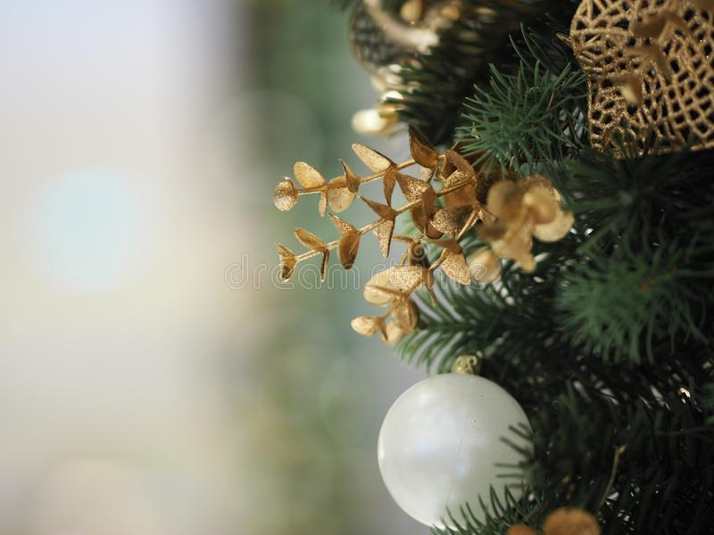 Christmas tree decorations have white ball, gold leaves on blurred of background. Closeup Christmas tree decorations have white ball, gold leaves on blurred of royalty free stock image