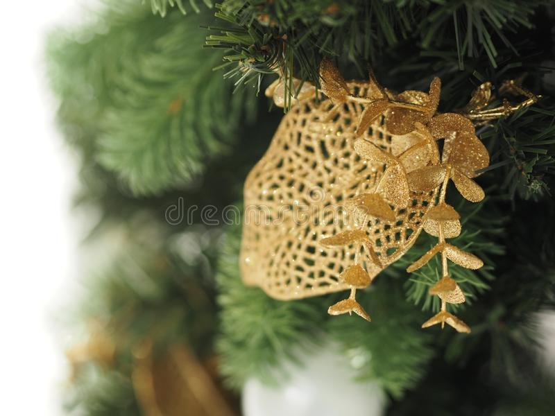 Christmas tree decorations have white ball, gold leaves on blurred of background. Closeup Christmas tree decorations have white ball, gold leaves on blurred of stock image
