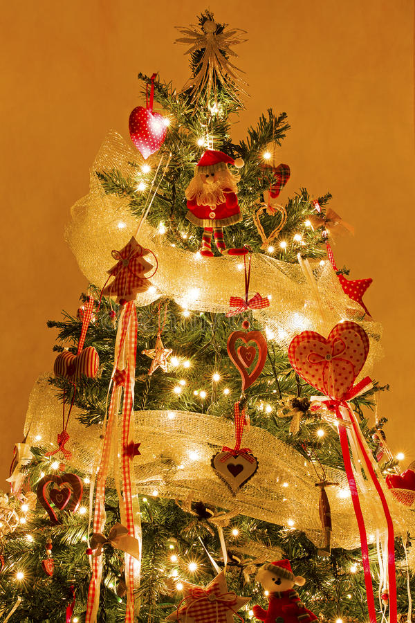 Christmas Tree with Decorations and Lights On. Indoor shot at night of Christmas tree decorated with fabric decorative items ( star heart santa claus etc... ) stock photo