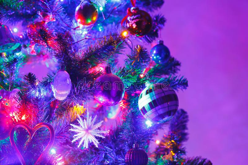 Christmas tree with decorations and purple illumination. Close-up view royalty free stock images