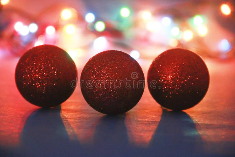 Christmas tree decorations red shiny balls on background of lights. Christmas tree decorations red shiny a  balls on  background of lights stock image