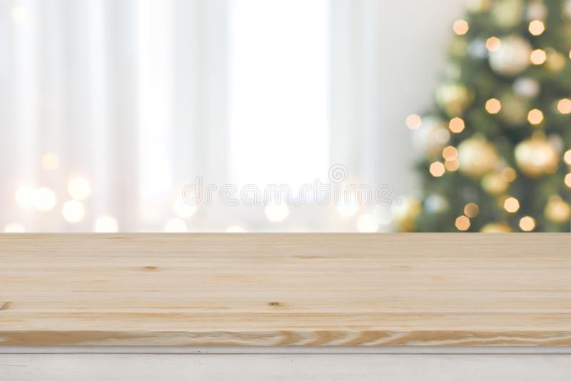 Christmas tree defocused background with wooden table in front.  stock photography