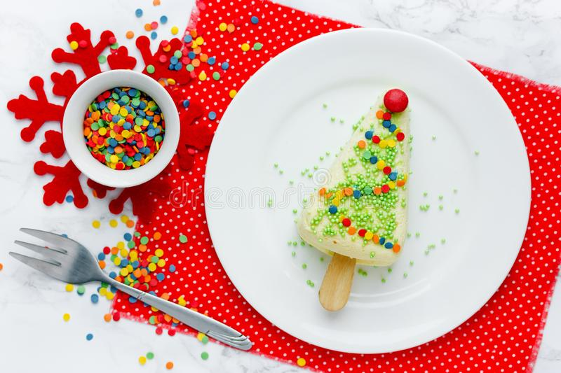 Christmas tree dessert - portion cheesecake on stick with colorful sugar sprinkles shaped christmas tree stock image