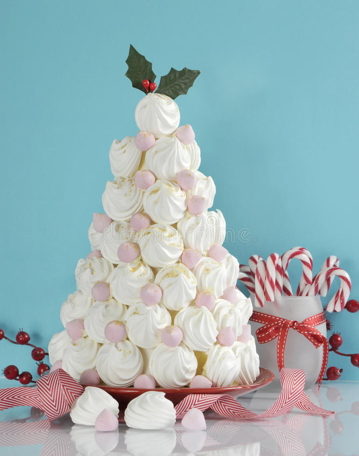 Christmas tree dessert treat made with pink and white meringues. With candy cane decorations against a blue and white background royalty free stock photos