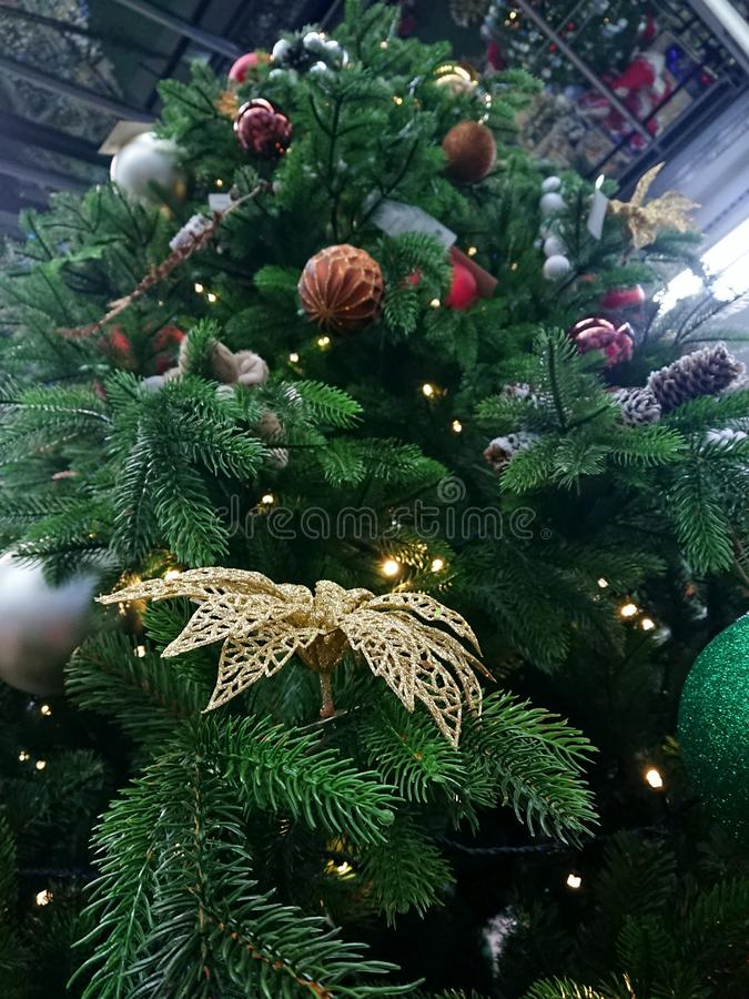 Christmas tree in different toys. Green Christmas tree in different holiday toys with a golden flower stock photo