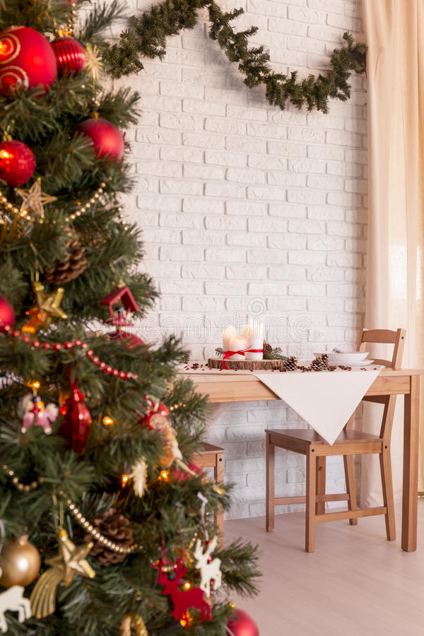 Christmas tree in dining room. Traditional red and gold Christmas tree in light dining room royalty free stock photo
