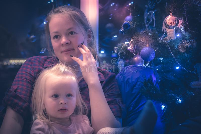 Christmas tree family happy mother embracing child daughter in dark living room with Christmas lights as Christmas Eve scene. Christmas tree family happy mother stock image