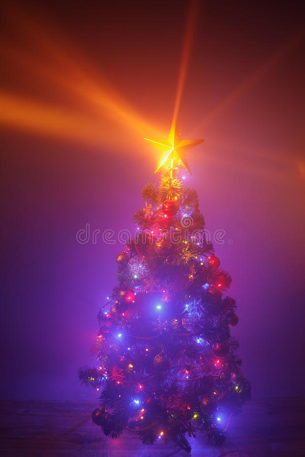 Christmas tree with festive lights, purple background with mist stock image