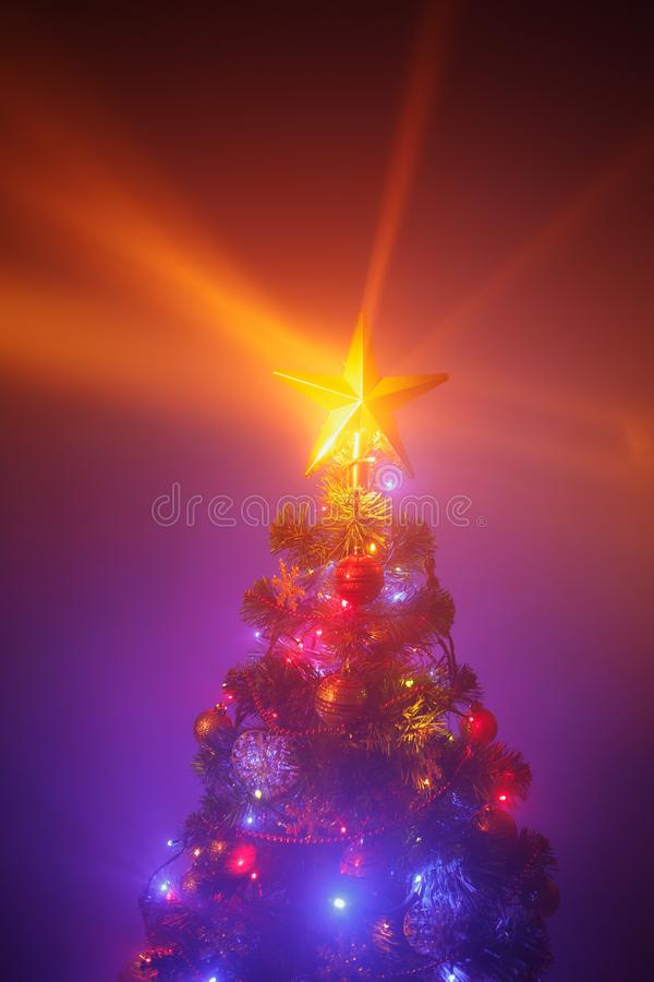 Christmas tree with festive lights, purple background with mist royalty free stock photos