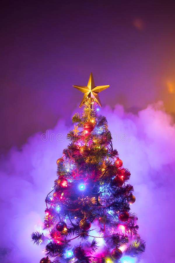 Christmas tree with festive lights, purple background with smoke royalty free stock photo