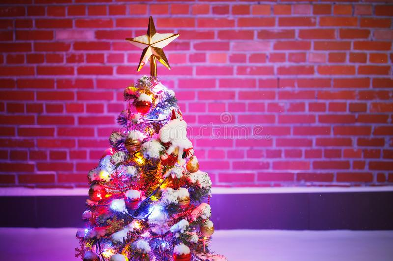 Christmas tree with festive lights in snow outdoors, purple brick wall background royalty free stock photo