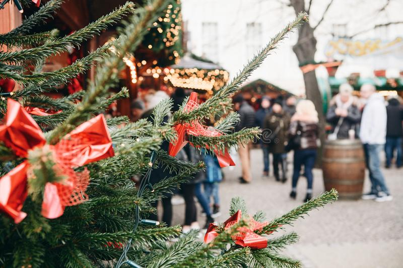 Christmas tree or fir branches in the foreground. The Christmas market in Germany is blurred in the background. Vacation. People relax during the holidays royalty free stock photos