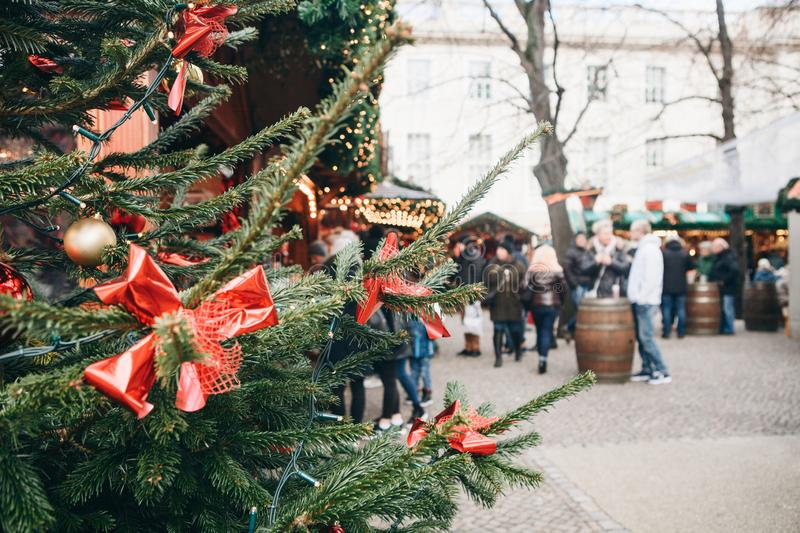 Christmas tree or fir branches in the foreground. The Christmas market in Germany is blurred in the background. Vacation. People relax during the holidays royalty free stock images