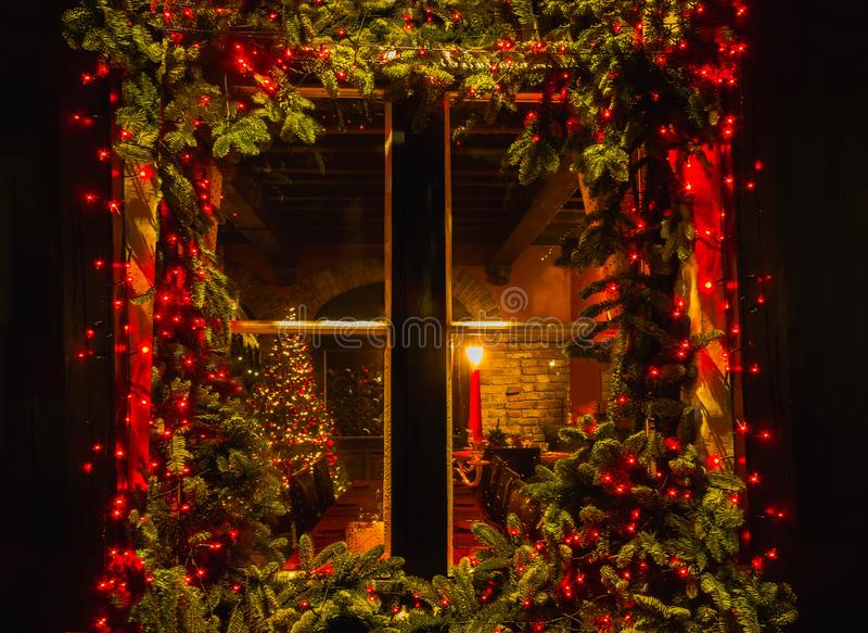 Christmas tree and fireplace seen through a wooden cabin window stock photography