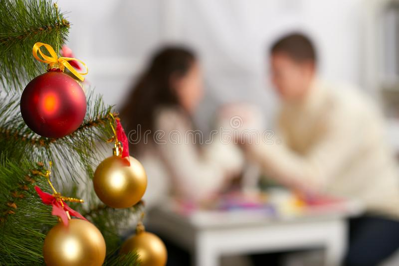 Christmas tree on foreground with defocused romantic young couple sit at the table, happy people and love concept, new year holida. Y stock photos