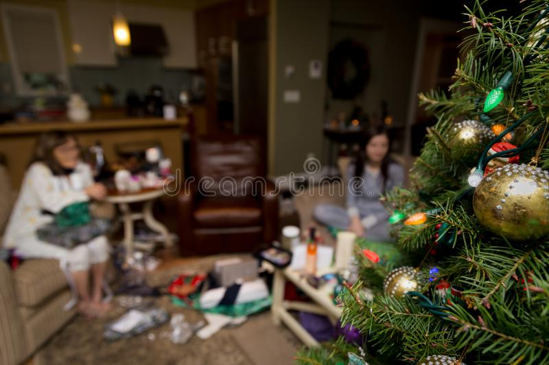 Christmas tree in the foreground with a family opening presents on christmas morning. Christmas tree in the foreground with a family opening presents on stock photography