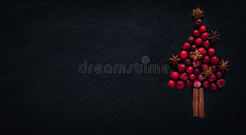 Christmas tree from frozen cherries, cinnamon sticks and star anise, on dark backround. Christmas concept royalty free stock photo