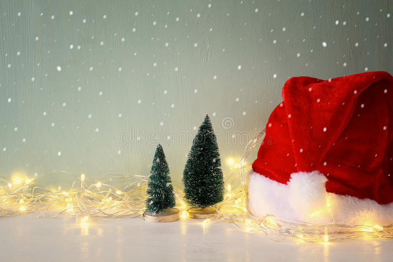 christmas tree with garland warm lights next to santa hat royalty free stock photography