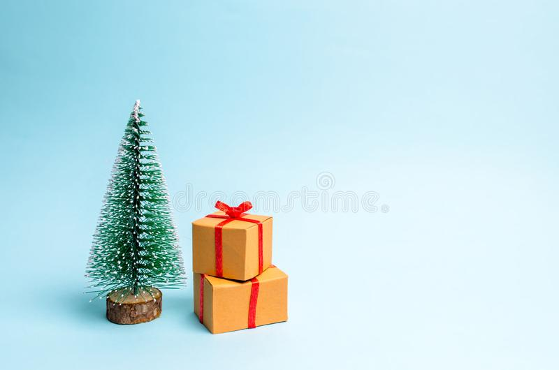 Christmas tree and gift on a blue background. Minimalism. Family holiday, Christmas and New Year. Sale of gifts. Sell-out. Surprise, birthday. Christmas party stock photography