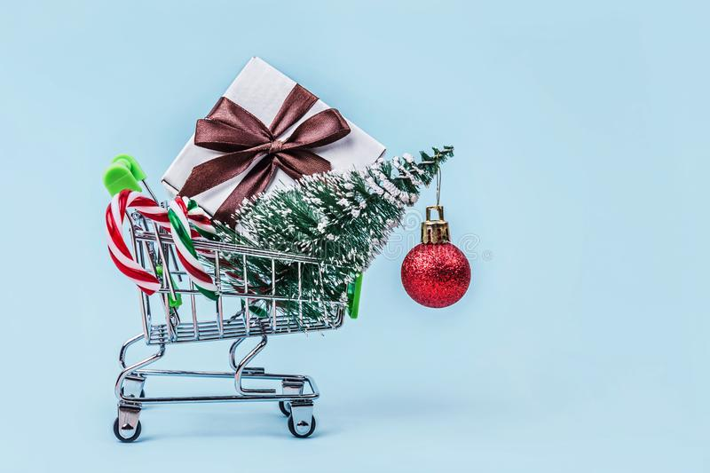 Christmas tree, gift box and candy canes in miniature shopping cart with on pastel blue background with copy space. stock photo