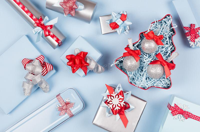 Christmas tree with glitter balls and gift boxes, decorations in pastel blue and silver metallic color with red silk ribbons. stock photo