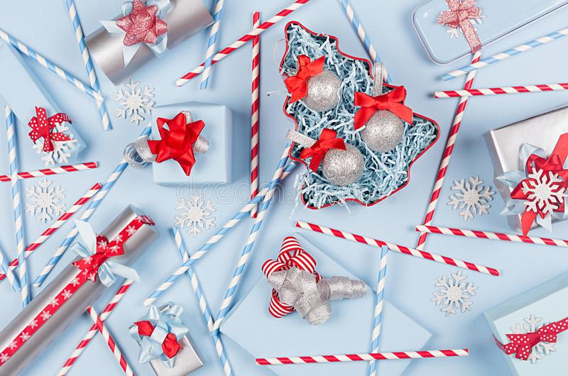 Christmas tree with glitter balls and gift boxes, decorations, straws in pastel blue and silver metallic color with red ribbons. Christmas tree with glitter royalty free stock photography