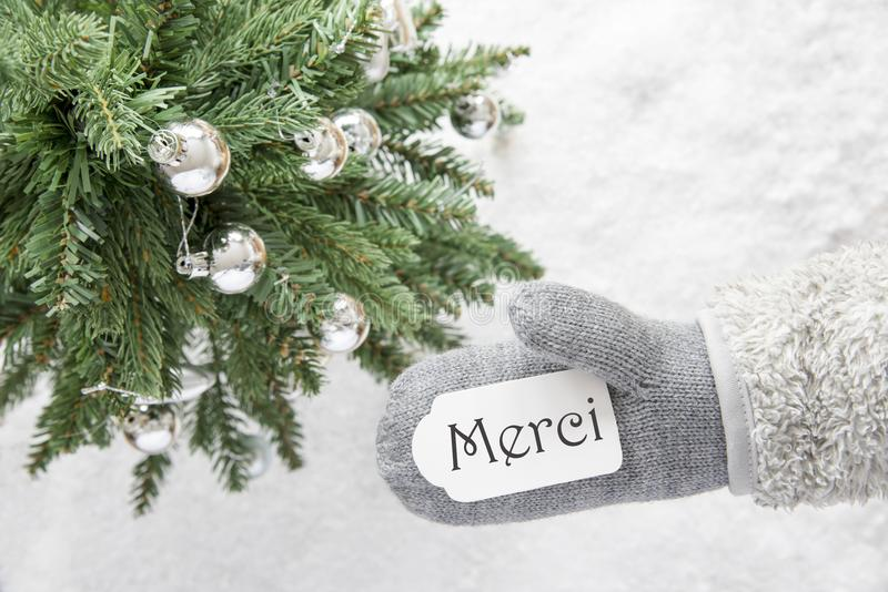 Christmas Tree, Glove, Merci Means Thank You. Glove With Label With French Text Merci Means Thank You. Green Christmas Tree With Silver Balls On Snow In stock photos