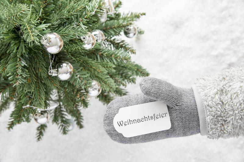 Christmas Tree, Glove, Weihnachtsfeier Means Christmas Party. Glove With Label With German Text Weihnachtsfeier Means Christmas Party. Green Christmas Tree With royalty free stock photos