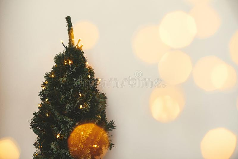 Christmas tree and golden lights bokeh in festive white room. Winter holidays preparation. Happy Holidays. Copy space. Little fir. Christmas tree royalty free stock photos