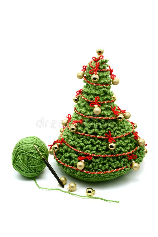 Christmas tree with goldnen balls crochet of wool. white isolated background. wool ball and crochet hook aside royalty free stock image