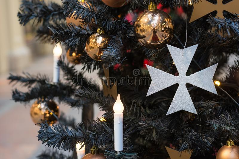 Christmas tree with gothic dark decor, golden balls, candles on dark in interiors. Xmas. Close up. Copy space royalty free stock image
