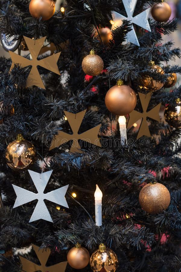 Christmas tree with gothic dark decor, golden balls, candles on dark in interiors. Xmas. Close up. Pattern stock image