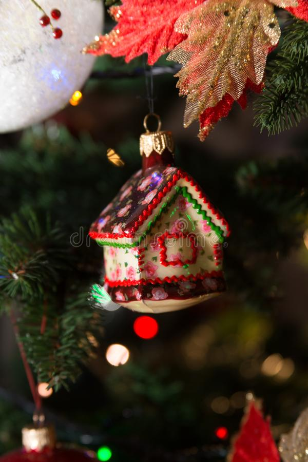 Christmas tree hand made ball gingerbread house. Nice hand made glass christmas tree ball hanged on the synthetic tree with turned lights. Shape of gingerbread stock photo