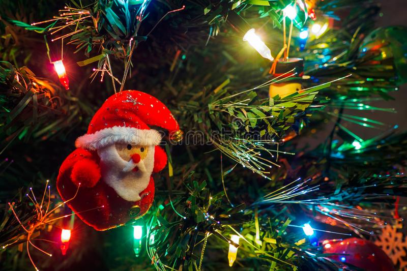 Christmas tree with hanging toy of Santa claus and garland lights. New year card, selective focus.  royalty free stock photography