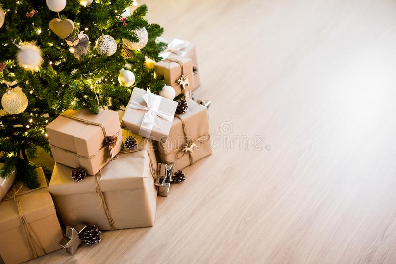 Christmas tree and heap of gift boxes - copy space over wooden floor background. Decorated christmas tree and heap of gift boxes - copy space over wooden floor stock images