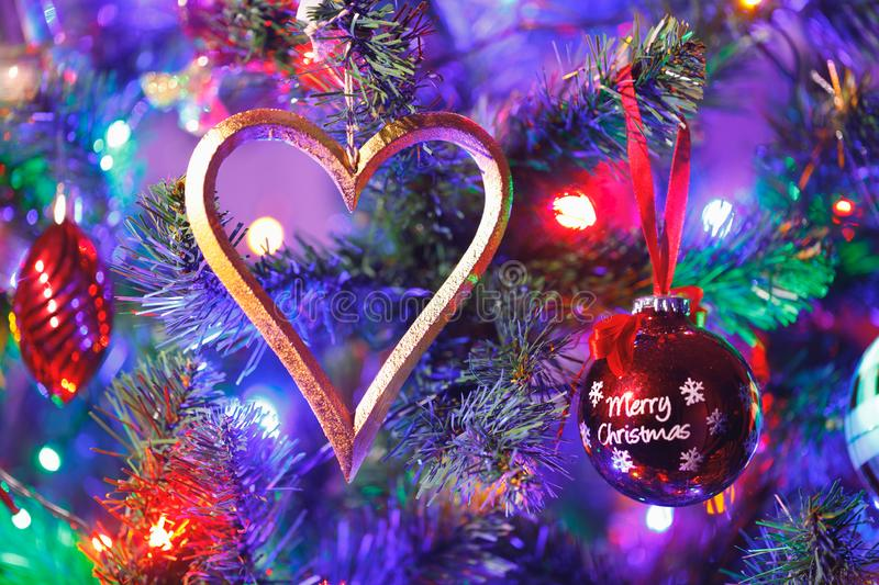 Christmas tree with heart shape decoration and purple illumination. Close-up view stock photography