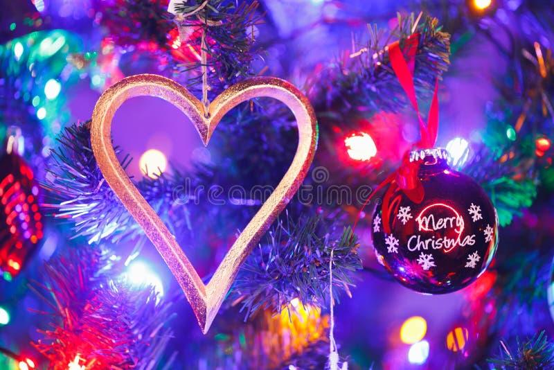 Christmas tree with heart shape decoration and purple illumination. Close-up view stock photo