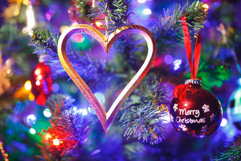 Christmas tree with heart shape decoration and purple illumination. Close-up view royalty free stock photography
