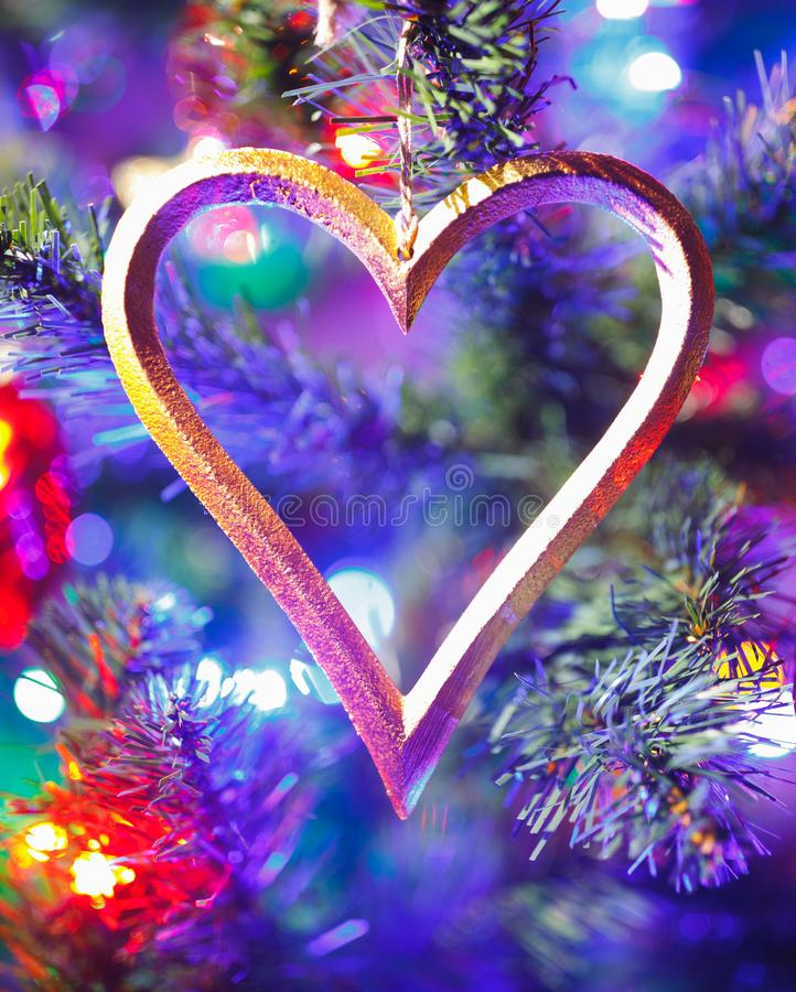 Christmas tree with heart shape decoration and purple illumination. Close-up view stock image