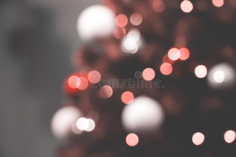 Christmas tree and holiday decorations. Blurred defocused background in colour of Living Coral. Holiday blurred background with New Year`s tree and decorations stock photo
