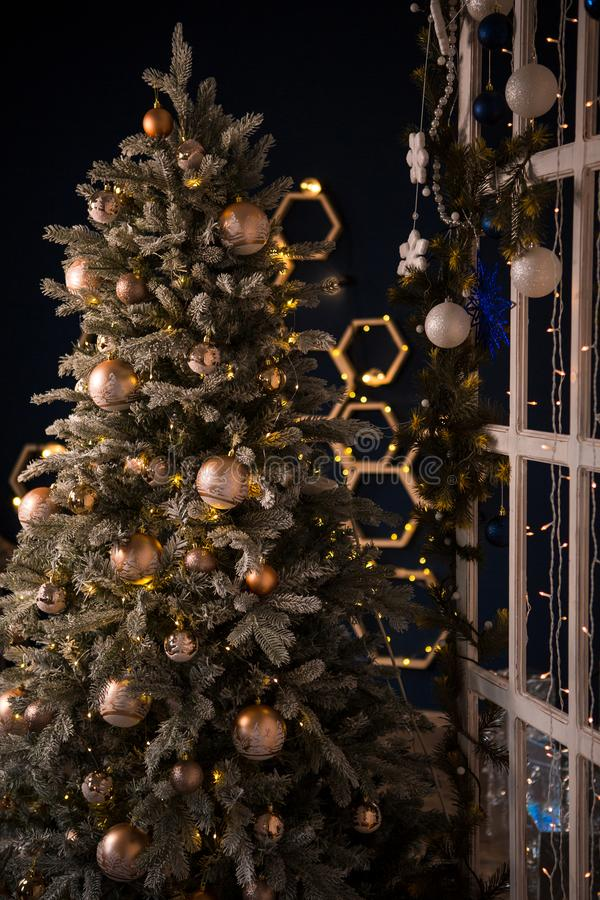 Christmas tree holiday home interior lights garlands, and home decorations. Details of the scenery of the new year. Red berries, Christmas lights, dark room royalty free stock image