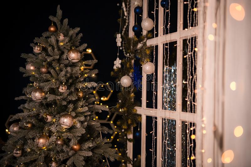 Christmas tree holiday home interior lights garlands, and home decorations. Details of the scenery of the new year. Red berries, Christmas lights, dark room stock images