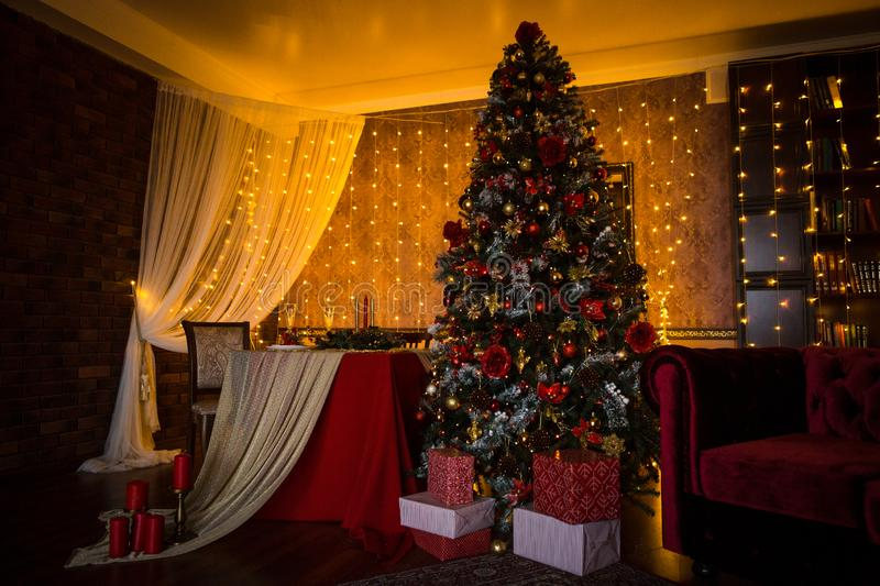 Christmas tree holiday home interior lights garlands, and home decorations. Details of the scenery of the new year. Red berries, Christmas lights, dark room royalty free stock images