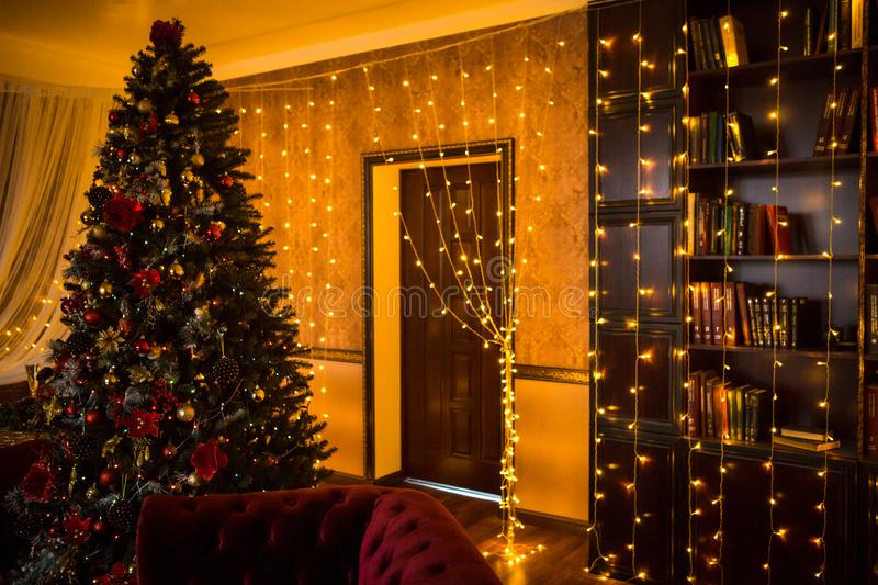 Christmas tree holiday home interior lights garlands, and home decorations. Details of the scenery of the new year. Red berries, Christmas lights, dark room royalty free stock photo