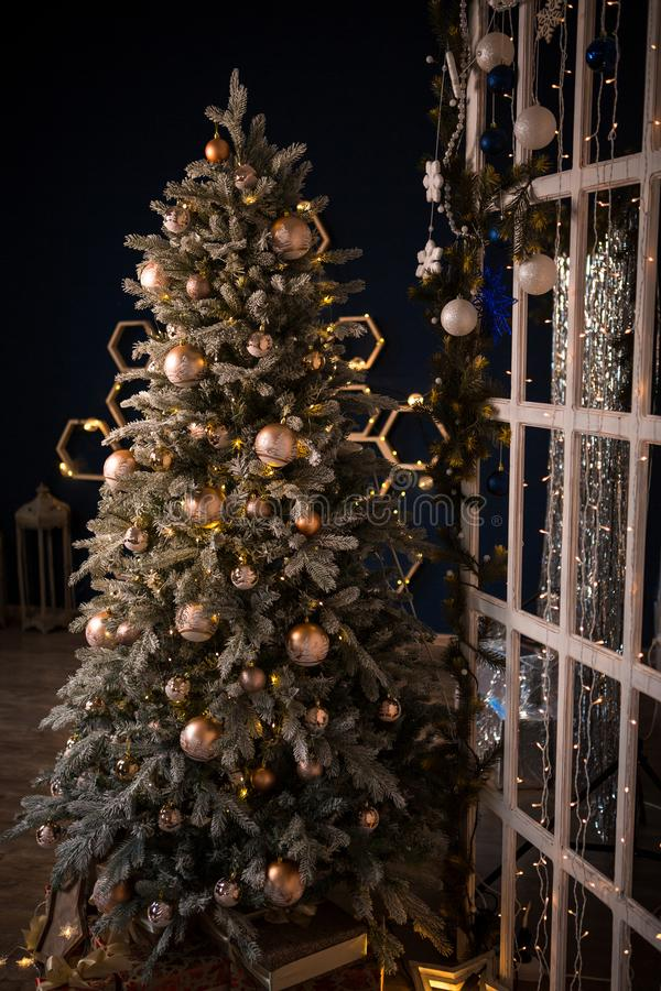 Christmas tree holiday home interior lights garlands, and home decorations. Details of the scenery of the new year. Red berries, Christmas lights, dark room stock photo